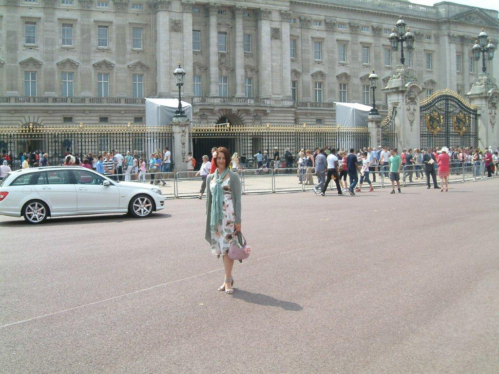 Nicole in front of the grand front gates of Buckingham Palace
